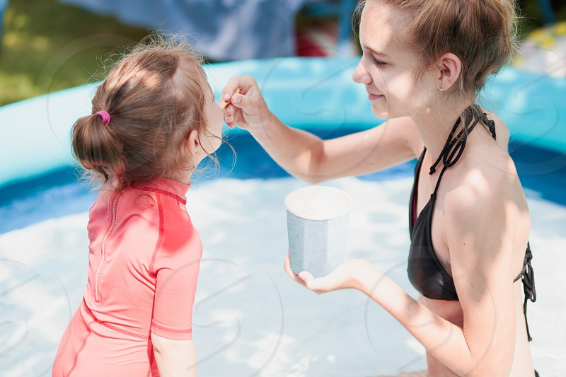 Teenage girl with her little sister spending time together in the swimming pool in a garden enjoy eating ice cream on a summer sunny day. Family quality time photo