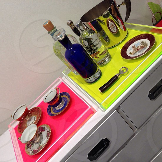 Neon trays with teacups and barware.  photo
