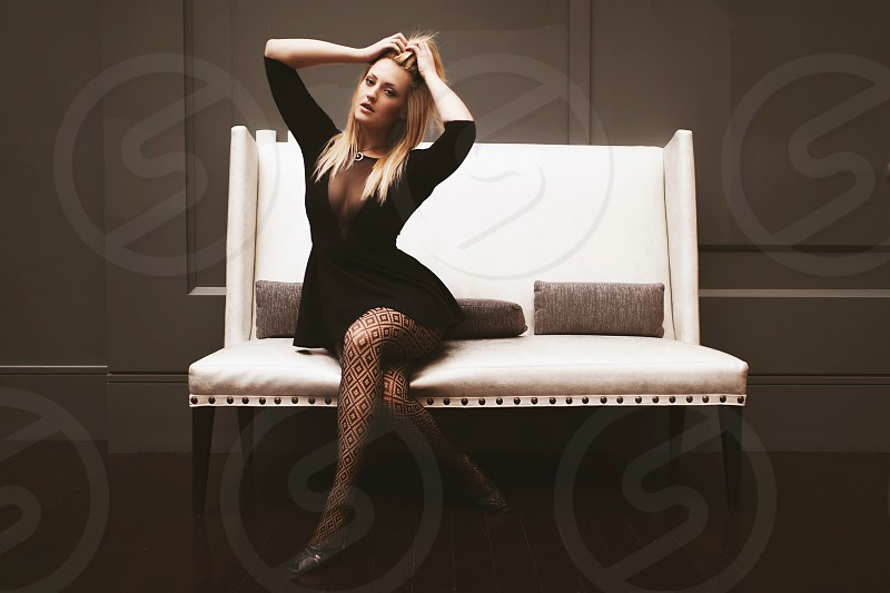 woman in black long sleeve dress sitting on white leather padded couch photo