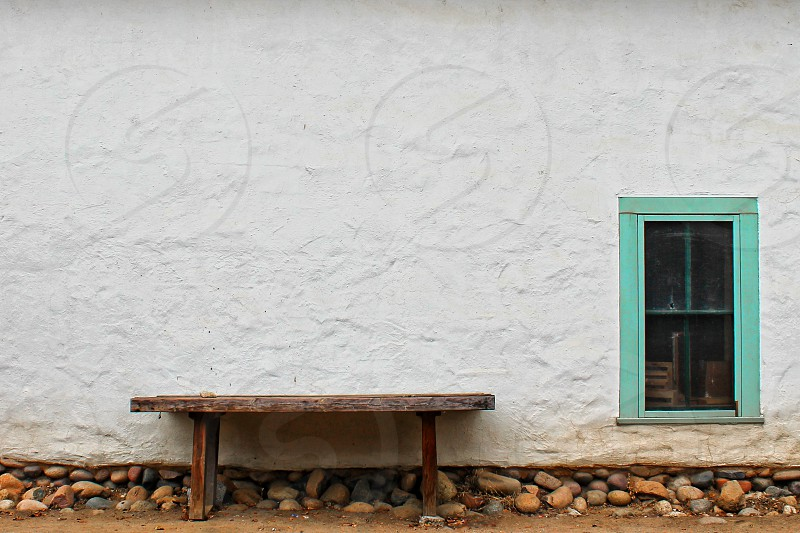 Wooden bench stands against a wall of an old white adobe house with an teal framed window photo