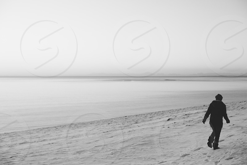 Silhouetted figure walking along a snowy coastline at sunset (black and white) photo