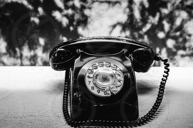 A black and white shot of an old disk telephone. photo