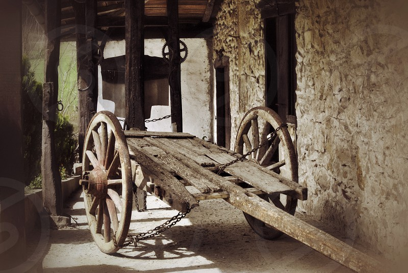 brown wooden cart beside brown wall photo