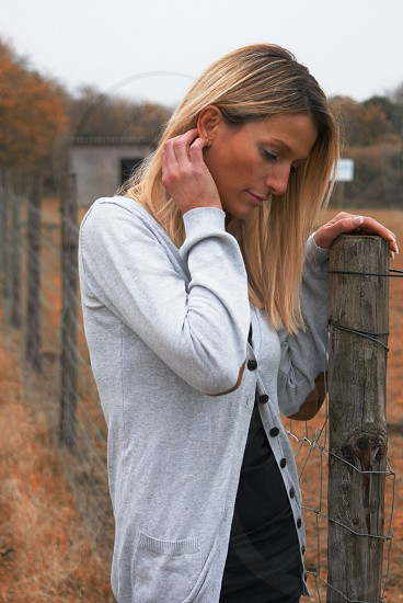 blonde woman wearing a white cardigan sweater standing by a chicken wire wood post fence photo