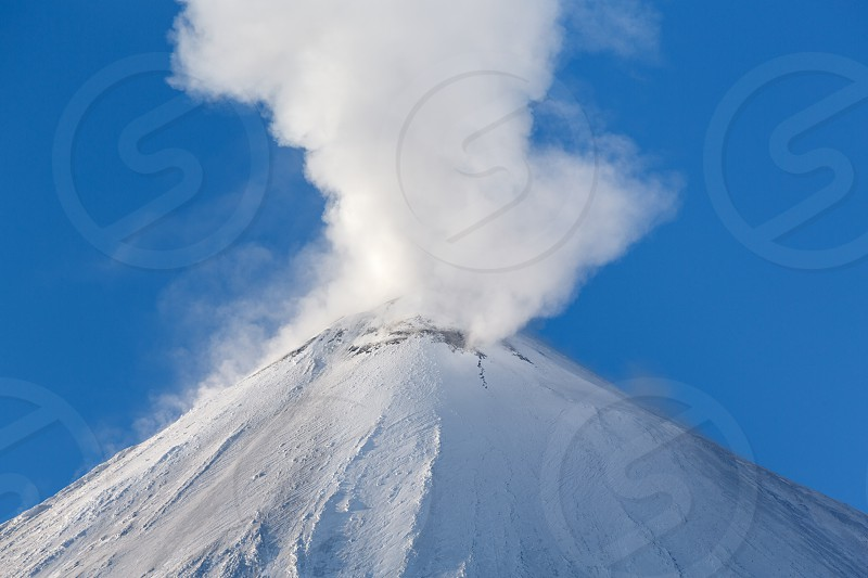 Winter volcanic landscape of Kamchatka: active Klyuchevskaya Sopka (Klyuchevskoy Volcano) view of the top of a volcanic eruption: emission from crater of volcano plume of gas steam and ashes. Eurasia Russian Far East Kamchatsky Krai Klyuchevskaya Group of Volcanoes. photo