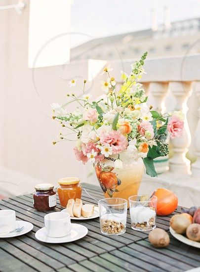 pink carnations and white flowers on beige ceramic vase on table surrounded with saucers and teacups jars and fruits photo