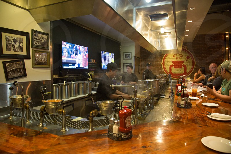 chrome metal air vents on top of a people cooking inside a restaurant with flat screen television photo