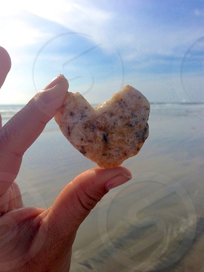 Fingers holding heart shaped rock Pacific Ocean beach sand glare photo