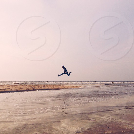 man wearing blue denim jeans jumping over shore during daytime photo
