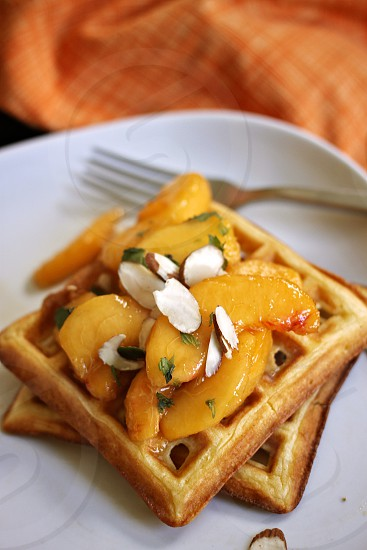 waffles fruit fresh peaches sliced almonds nuts healthy breakfast mint fork napkin orange photo