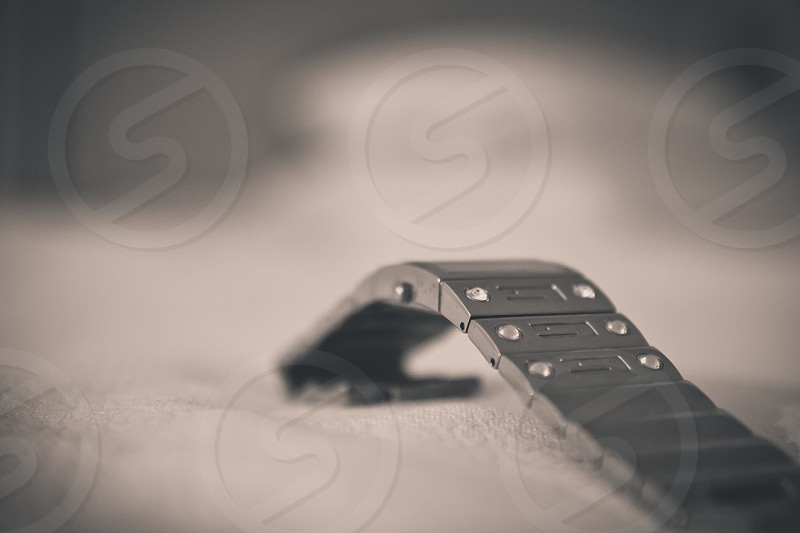 Close-up of a metal watch strap is on a white cloth.White stones embedded on the watch strap.Blurred background. photo