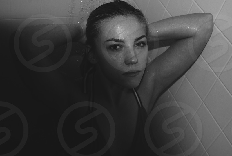 grayscale photo of a woman in black halter brassiere holding her hair water drops from the shower in the bathroom photo