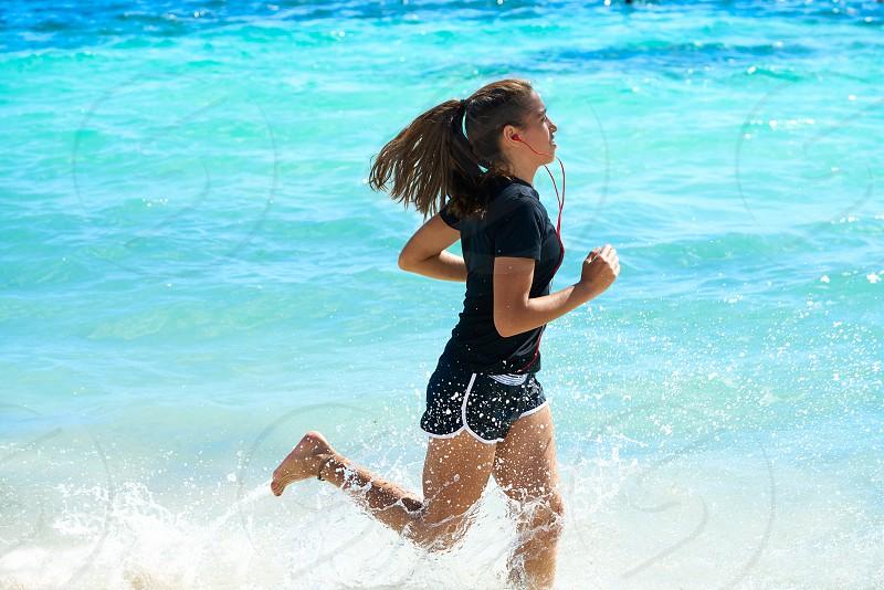 Latin girl running in caribbean shore beach of Mayan Riviera of Mexico photo