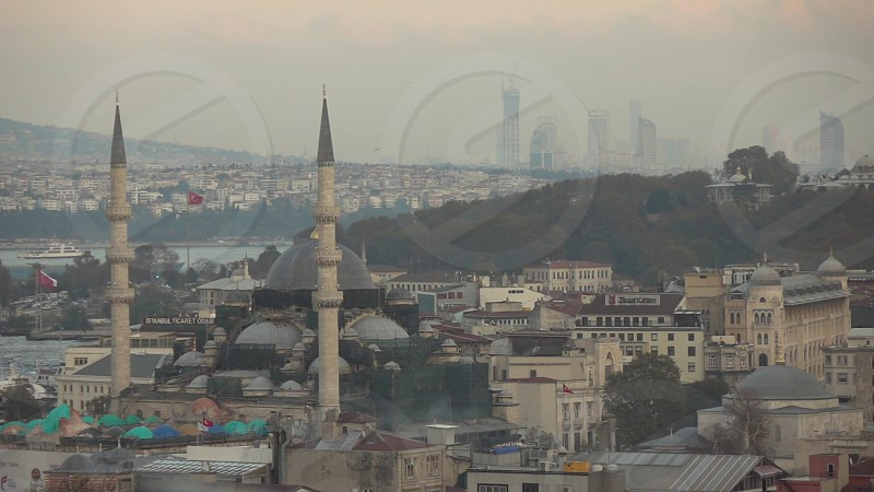 View sityscape of old part Istanbul vith Rustem Pasha Mosque at Eminonu. Flying seagulls across in a summer day at sunset. Slow motion Full HD video 240fps 1080p. photo