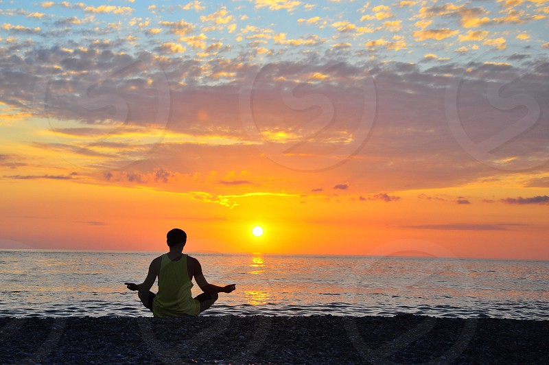 person wearing white tank top and shorts seated on beach side meditating overlooking sunset photo