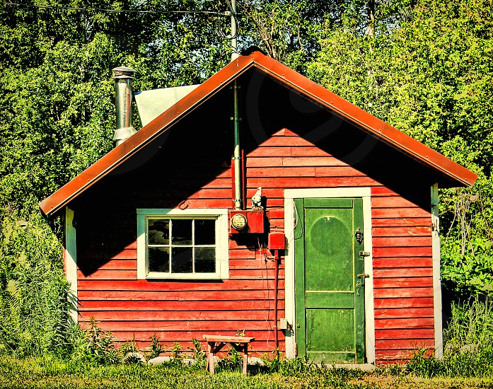 Rural red wooden home has a bright green door. photo