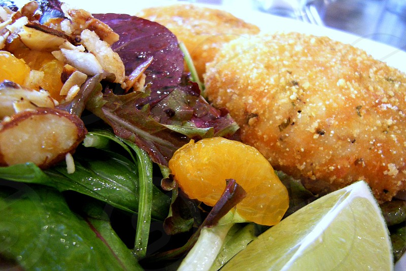Salmon cakes on salad of greens mandarin oranges almonds and limes. photo