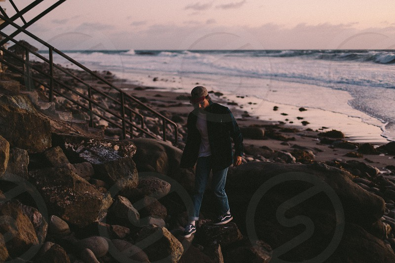 person wearing jacket and walking on rocky seashore near staircase photo