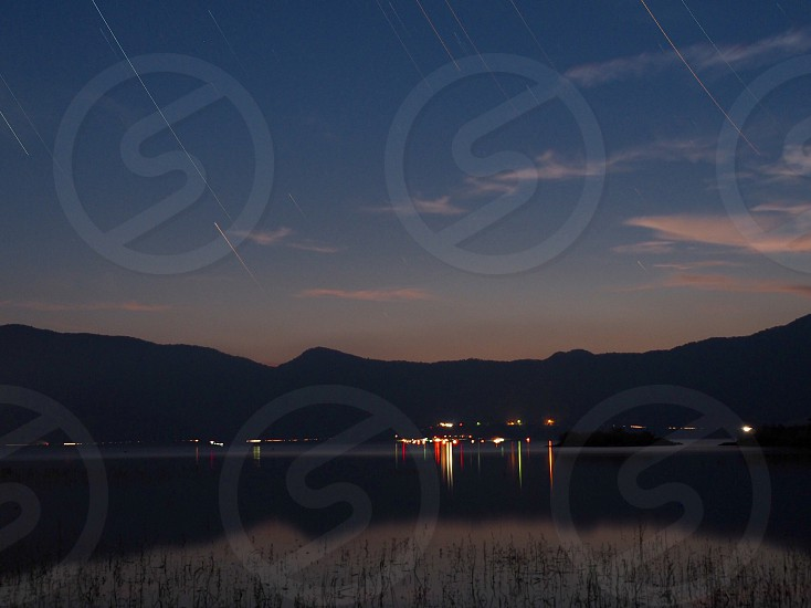 photo of mountain near body of water at nighttime photo