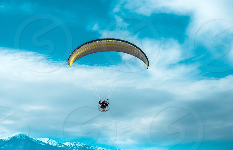 Paragliding fly on blue cloudy sky photo