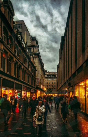 people walking along the street near shops between building during cloudy sky photo
