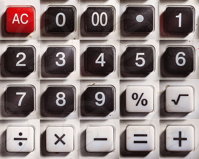 Numbers and mathematical signs of an old dusty calculator.  photo