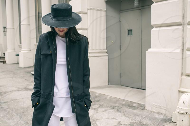 woman in black coat standing near grey door photo
