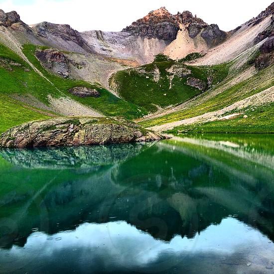 green lake beside grassy mountain photo