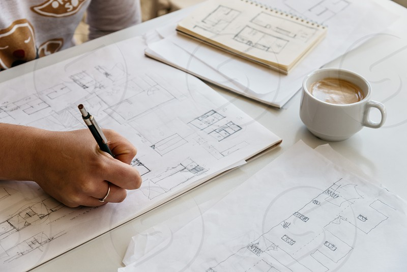 Young female architect working on sketches with a cup of coffee photo