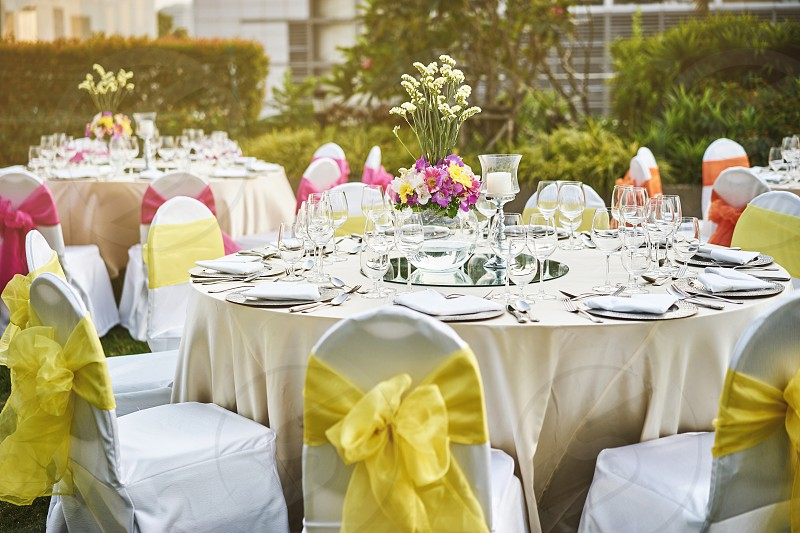 Luxury wedding reception dinner table setting with empty glasses of water wine and dinnerware with flower decoration and white fabric cover chairs with yellow sash photo