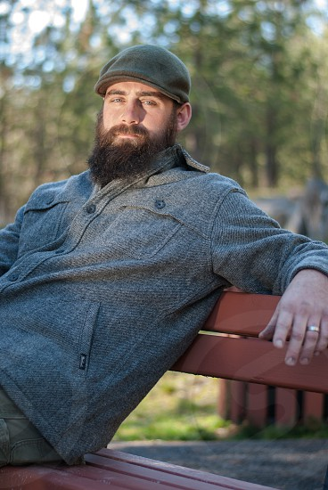 Bearded man sitting on bench in the fall looking at camera photo