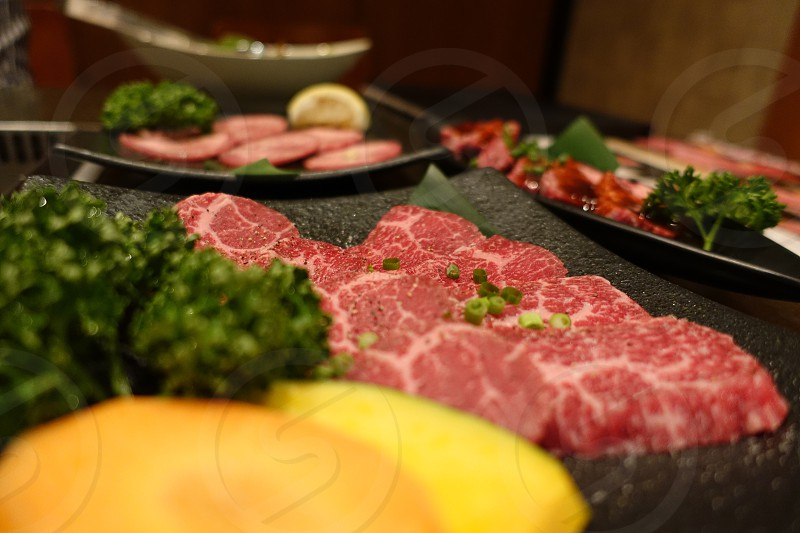 red raw meat with green leafy vegetables photo