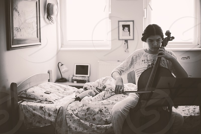 Teenage girl plays cello in her room in black and white.  photo