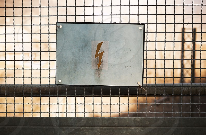 Sign for attention of electrical shock on metal gate. photo