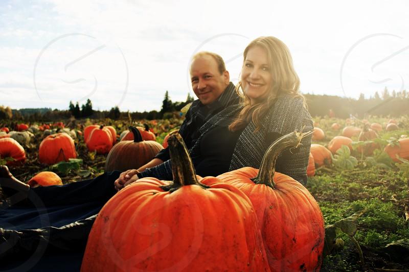 couple behind orange pumpkin photo