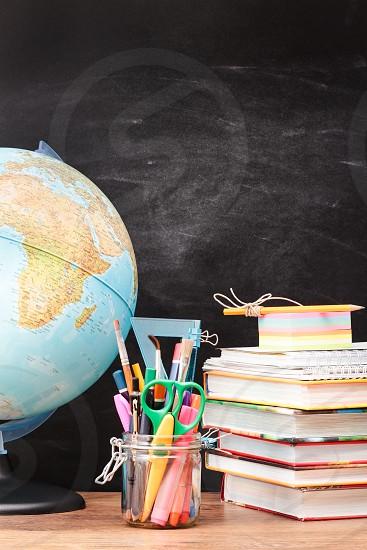 School accessories on desktop with blackboard in the background photo