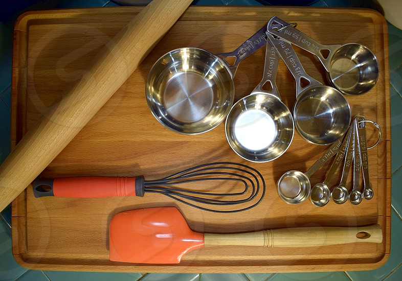 Essential bakers tools: measuring cups measuring spoons rolling pin whisk and spatula.  photo