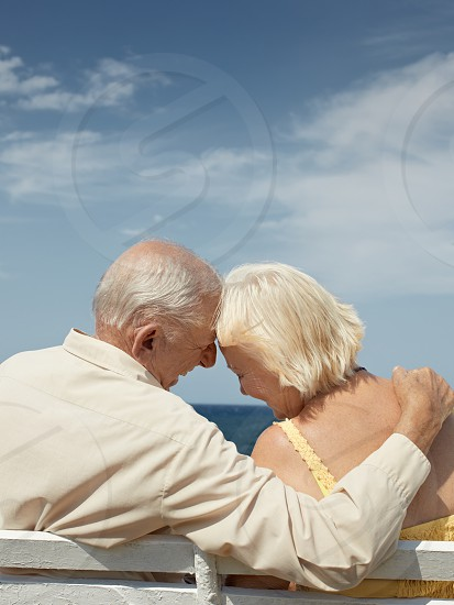 happy; hugging; woman; man; love; couple; elderly; 60s; 70s; adults; affection; aged; bench; carefree; casual; caucasian; copy space; embracing; emotion; female; future; hug; husband; loving; male; marriage; ocean; old; outdoor; people; persons; rear view; relationship; relax; retired; retirement; romance; sea; senior; seniors; serene; sitting; sky; smiling; summer; tenderness; together; two; vacations; wife photo