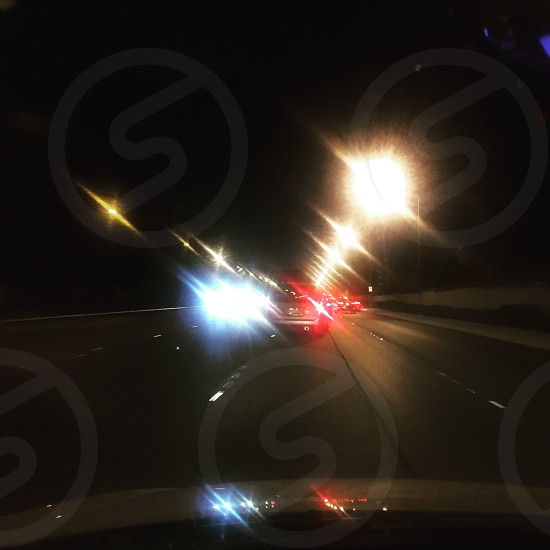 gray vehicle in front flashing taillight with many more vehicle up ahead on lighted highway during nighttime photo