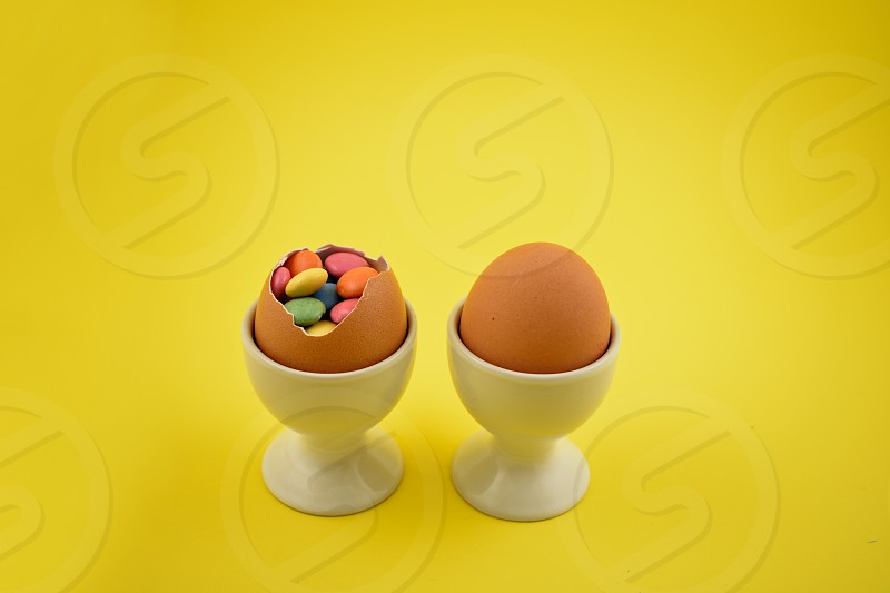 Candy easter eggs. Easter eggs on a yellow background. Spring decoration images. Easter decoration. Sweet egg with surprise. Egg filled with candy. Easter concept photo
