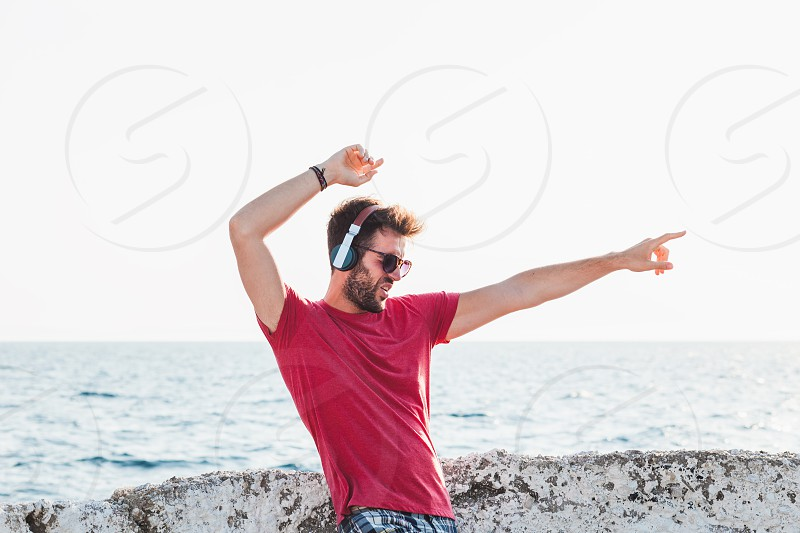 Young man listening to the music on headphones by the sea photo