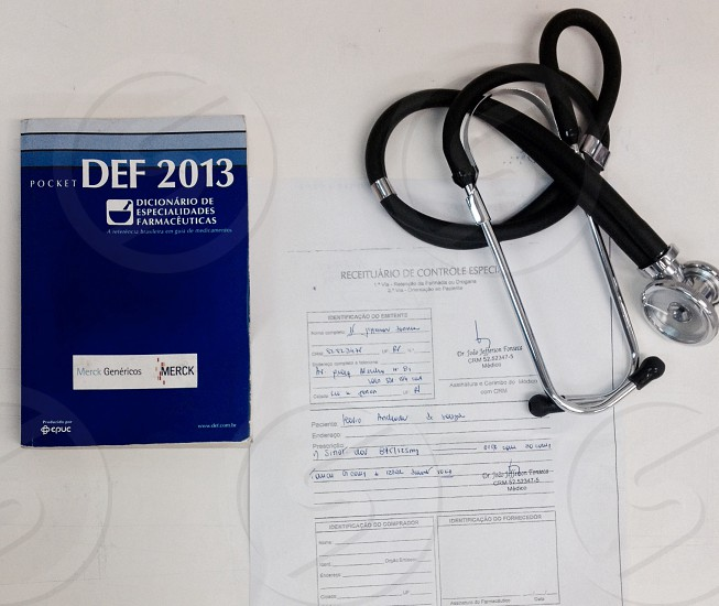 white document under black and stainless steel stethoscope next to blue and grey striped def 2013 book on white surface photo