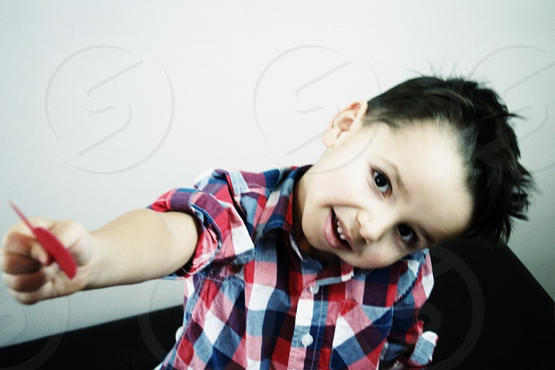 boy in red blue and white checked smiling photo