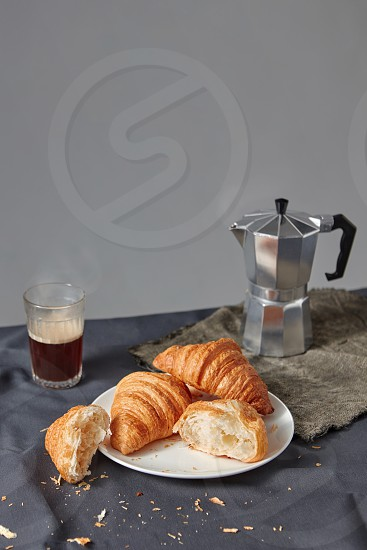 Glass of aromatic hot coffee and plate with freshly baked french croissants on a grey background. Continental breakfast concept. Place for text. photo