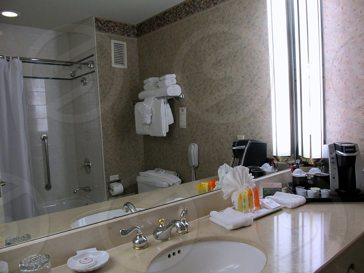 Hotel bathroom with amenities sink and reflection of bath stall photo