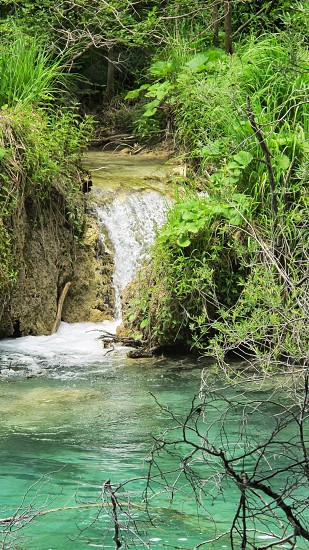 Waterfalls draining into turquoise water from limestone cliffs photo