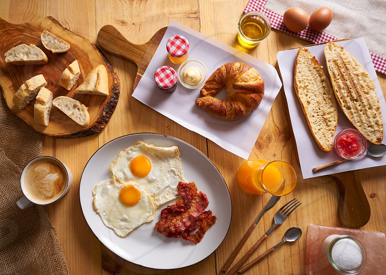 Continental breakfast croissant eggs bacon bread slices orange jiuce photo