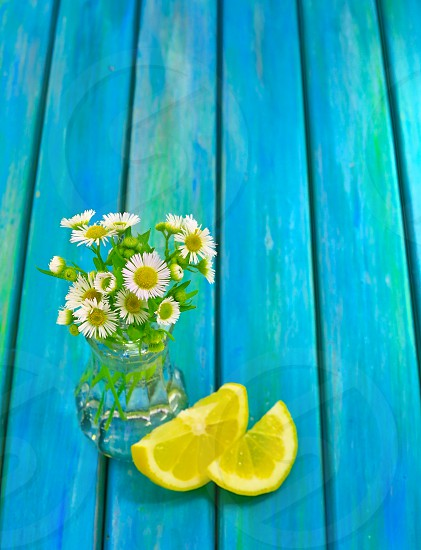 lemon slice and lime slice next to small vase of dasies on blue table photo
