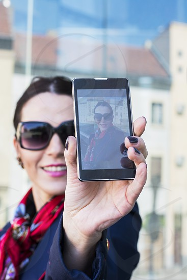 Beautiful businesswoman capturing herself on her smartphone photo