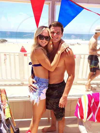 woman in blue bikini top hugging a man photo